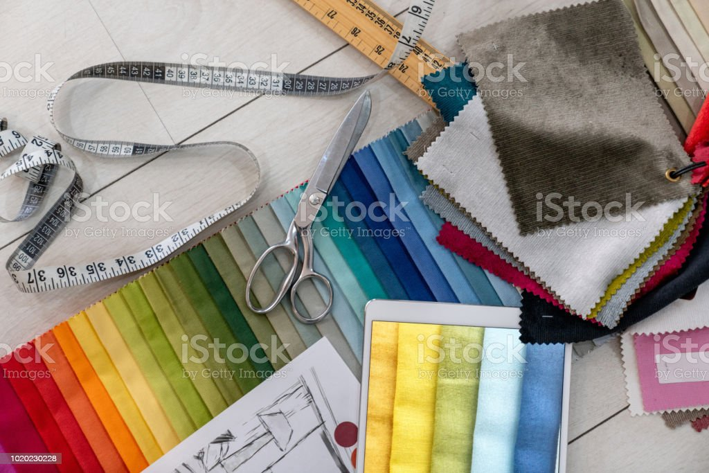 Fabric swatches and tailoring tools on the table of a textile shop stock photo
