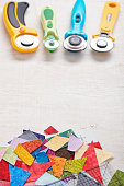 Fabric waste on craft mat, four roller cutter, text space at center