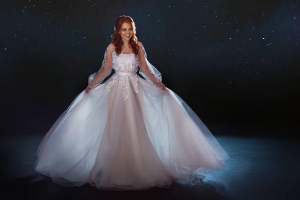 Novia fabulosa en un vestido hermoso entre las estrellas. Joven hermosa mujer en vestido de Novia de falda amplia luz - foto de stock