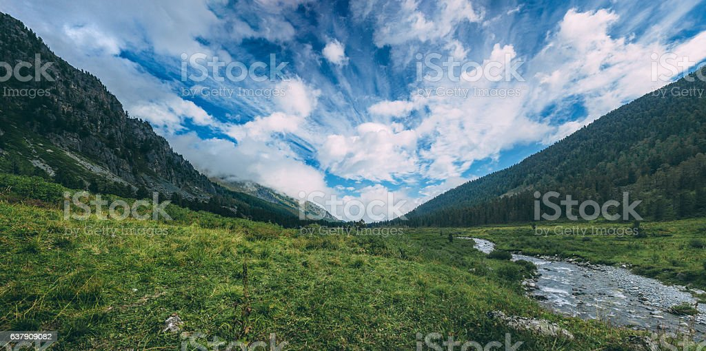 Fabulous clouds in the middle of the green hills stock photo