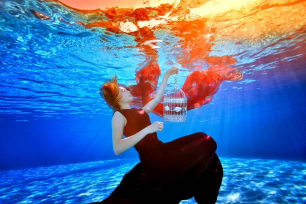 eine fabelhafte mädchen in einem wunderschönen kleid in einem pool schwimmt und träume auf dem hintergrund der hellen lichtern. sie hat einen weißen käfig in der hand und sinkt auf den boden des pools mit geschlossenen augen. porträt. - meerjungfrau kleid stock-fotos und bilder