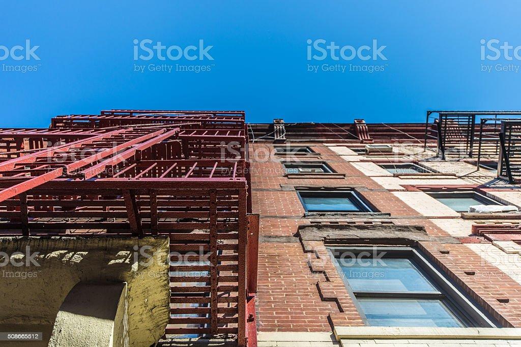 Facade and fire escape of pre-war walkup red brick apartment building...