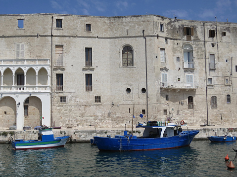 istock facade and quay in Polignano a Mare with boats and fishing gear 1036915790