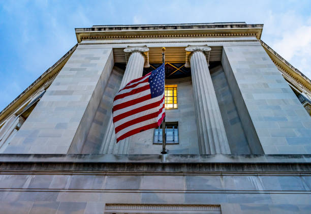 Facade Flags  Justice Department Building Washington DC Facade FlagsJustice Department Building Pennsylvania Avenue Washington DC Completed in 1935. Houses 1000s of lawyers working at Justice. federal building stock pictures, royalty-free photos & images