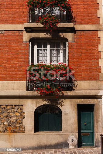 facade of a brick house. Balconies with flowers. Paris, France.