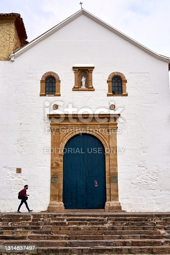 Young woman walking past the entrance facade of a church in a Colombian country town. Villa de Leyva. Boyacá Department. Colombia. April 7, 2021.