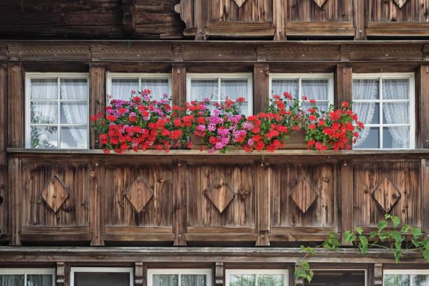 Fassade eines Bauernhauses in Appenzell, Schweiz, mit Geranienblüten – Foto