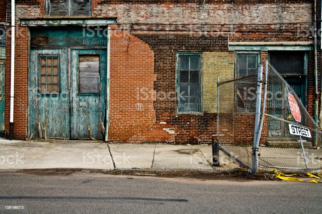 Facade of a grungy abandoned urban warehouse stock photo