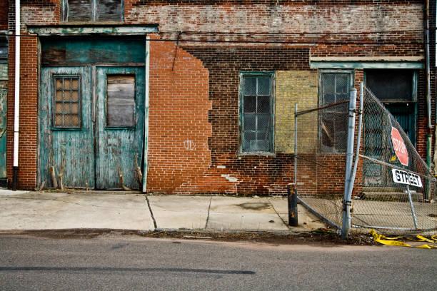 facade of a grungy abandoned urban warehouse - slechte staat stockfoto's en -beelden