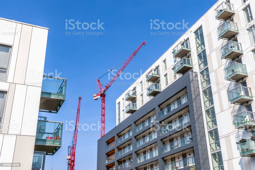Facade of a modern flat with building cranes in the background royalty-free stock photo