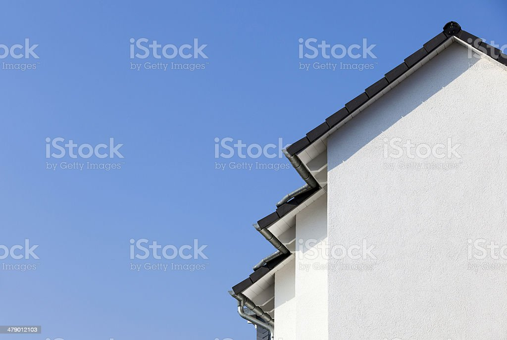 facade of a new house with blue sky in background stock photo