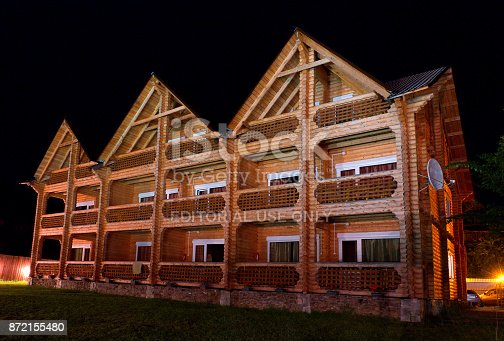istock Facade of a traditional russian wooden hotel (exterior) in the Altai touristic region (Russia) by a summer night with dark black sky as a background. 872155480