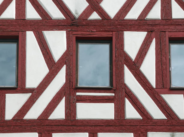 Facade of an half-timbered house with red timber and windows stock photo