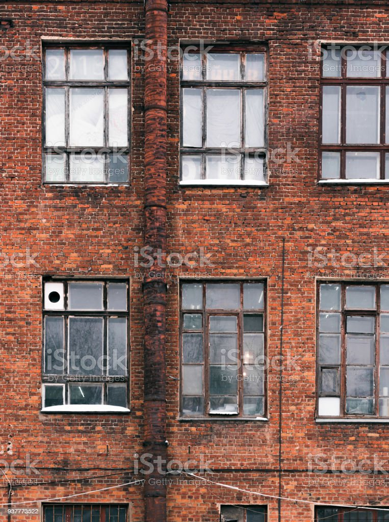 Facade of an old brick building in loft style. High Windows and...