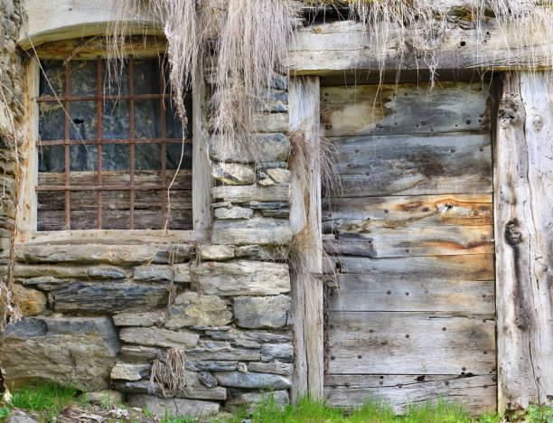fachada de una antigua casa de piedra y madera en un pueblo abandonado - foto de stock