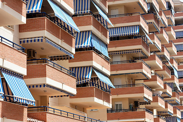 Facade of apartment building with balconies and awnings from sun.