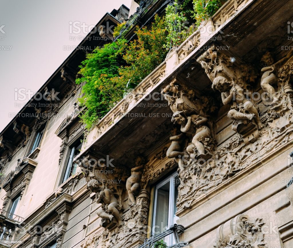 Facade of building in Porta Venezia neighbourhood. Ornamental humanist statues hanging from the wall. Architecture is early 1900s nature inspired Liberty, art-noveau style zbiór zdjęć royalty-free