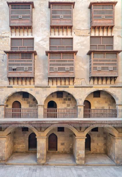 gevel van forten (wikala) van bazaraa, met gewelfde arcades en windows vallende interleaved houten rasters (mashrabiyya), middeleeuwse cairo, egypte - karavanserai stockfoto's en -beelden