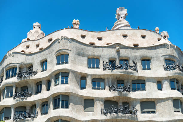 Facade of Casa Mila in Barcelona Barcelona: Facade of Casa Mila with green trees on the street of Barcelona, Spain. Famous building designed by Antoni Gaudi, included in the UNESCO list passeig de gracia stock pictures, royalty-free photos & images