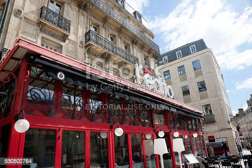 Dijon, France -- April 8, 2016: Facade of L'Edito cafe at Place Darcy in Dijon, France, incidental people can be seen on the street.