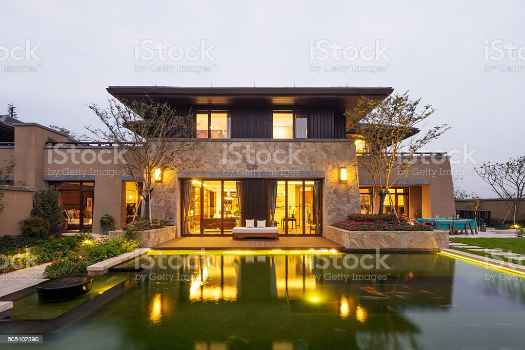 facade of modern building near pond at dusk stock photo