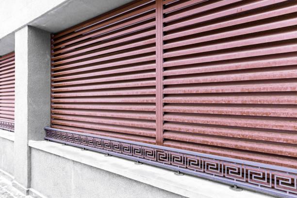 facade of modern building with red metal protective blinds and wrought metal railings - com portada imagens e fotografias de stock