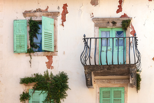 Facade of old shabby building with green shutters and balcony.