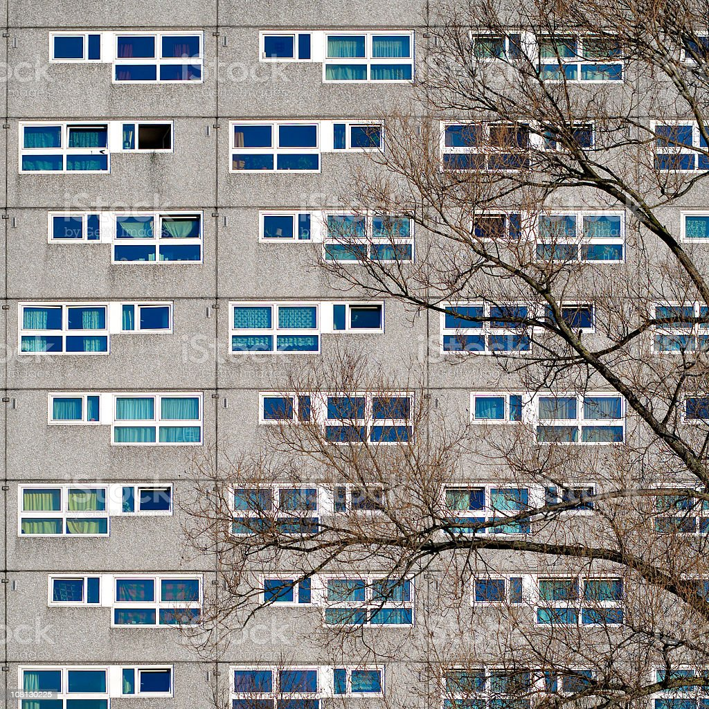 Facade of prefabricated architecture with several windows and one tree royalty-free stock photo