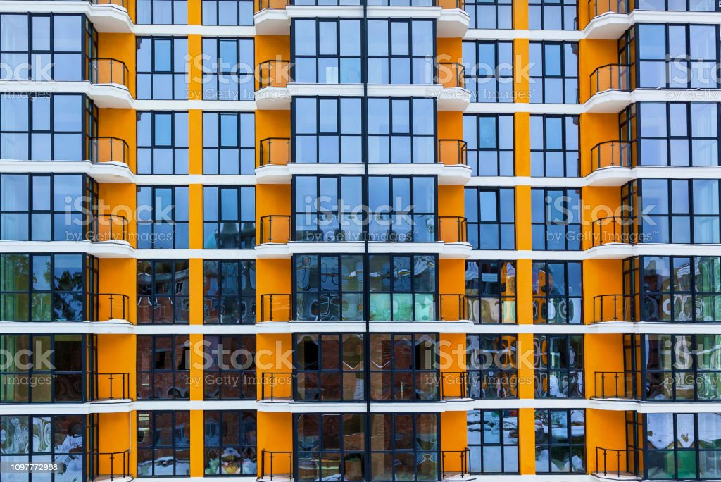 The glass facade of residential apartments in a high-rise building....