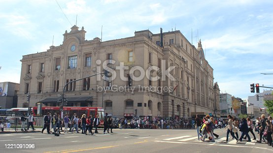 Facade of the Once Railway Station (taken from the Pueyrredón Avenue), with some buses and a large crowd of people during the summer, Buenos Aires, Argentina