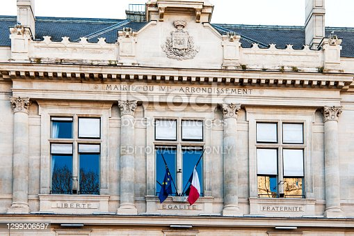 istock Facade of the town hall of Paris VIe, with flags and motto 1299006597