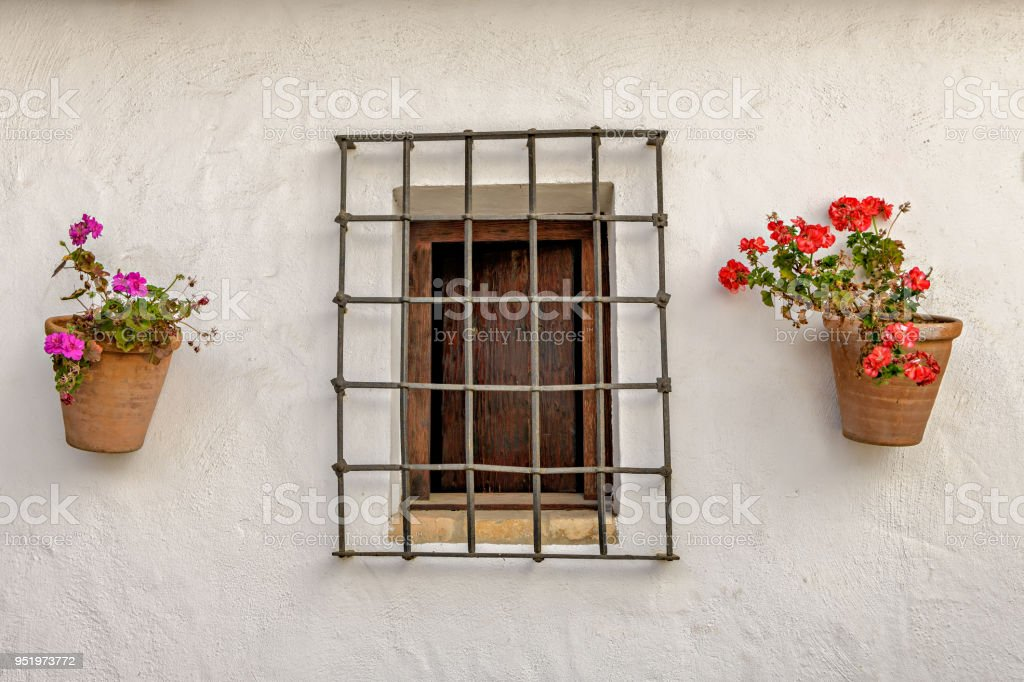 Facade of traditional Spanish house with flower pots with geraniums and fenced window. stock photo