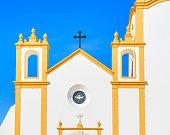 Facade of typical church in Luz town against blue sunny sky, Algarve region, Portugal