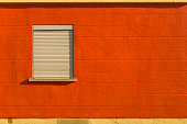 Facade with bright colors red orange yellow pedestal and a window shutter sideways horizontal line pattern