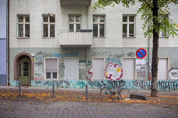 Facade with closed windows and grafitti stock photo