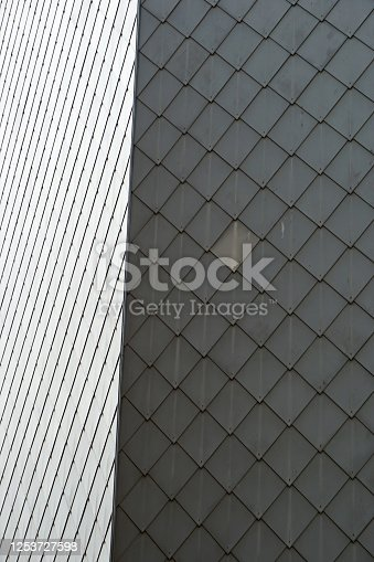 Architectural detail: facade with a pattern of grey tiles.
