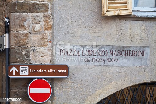 Facade with street sign and fingerpost to cable rope car in Bergamo seen in Citta Alta. Building is at square Piazza Lorenzo Mascheroni.