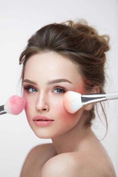 Face Beauty Cosmetics. Beautiful Girl With Makeup Applying Blush stock photo