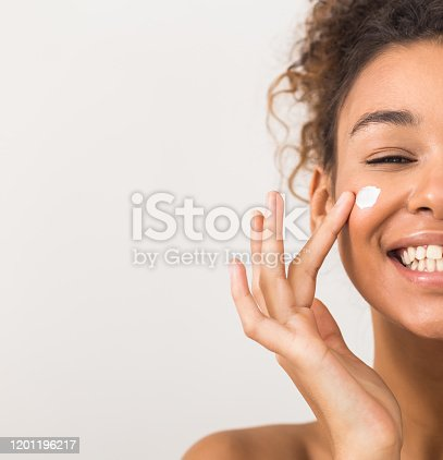 Face care. Happy black woman applying moisturizer cream on cheek, half face portrait, light background with copy space