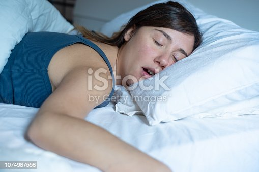 istock Face close up portrait of woman sleeping in bed and snoring 1074987558