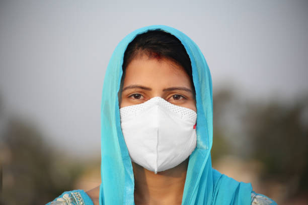 Face close-up of young women covering her face with pollution mask for protection from viruses like COVID-19 stock photo