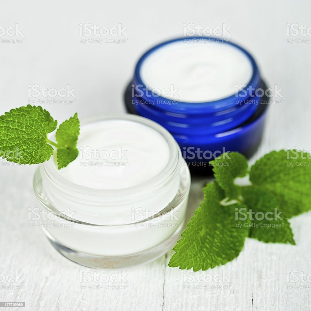 face cream in jars with urtica leaves royalty-free stock photo