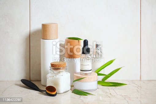 Face cream, serum, lotion, moisturizer and sea salt  among bamboo leaves in the bath