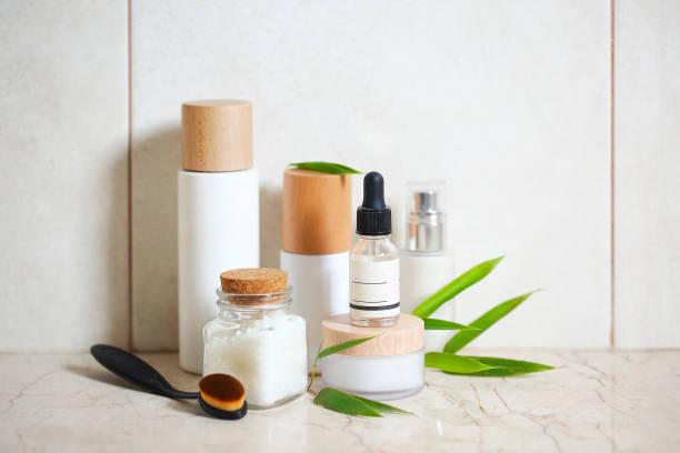 creme de rosto, soro, loção, hidratante e sal marinho entre folhas de bambu - mercadoria - fotografias e filmes do acervo