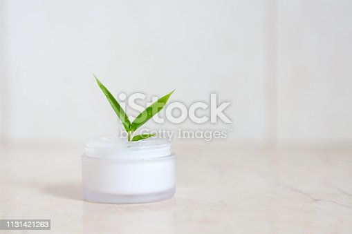 Face cream with bamboo leaves over light background in the bathroom