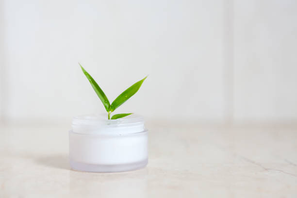 Face cream with bamboo leaves over light background stock photo