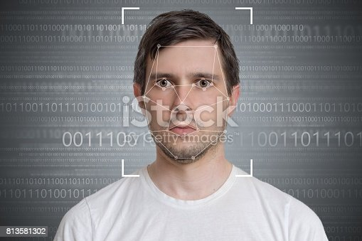 istock Face detection and recognition of man. Computer vision concept. Binary code in background. 813581302