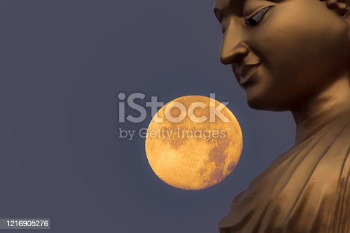 Face Golden Buddha statue at night with a full moo