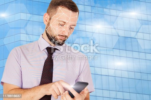istock Face identification or iris authentication in smartfone. Young handsome bearded business man holding tablet or phone and pass 1178816637