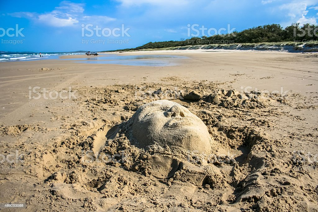 Face in sand on beach stock photo